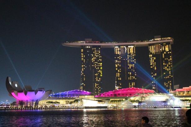 Mulai muncul cahaya laser ungu pink dari bangunan2 di bawah.